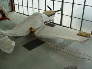 Globe Swift covered and in hangar.