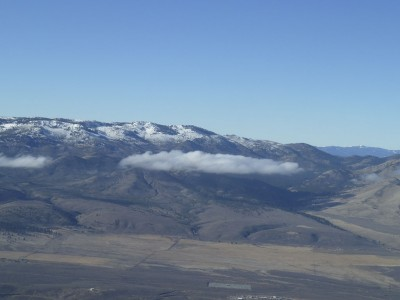 Single cloud that formed below the top of a mountain ridge west of the Reno-Stead (KRTS) Airport.